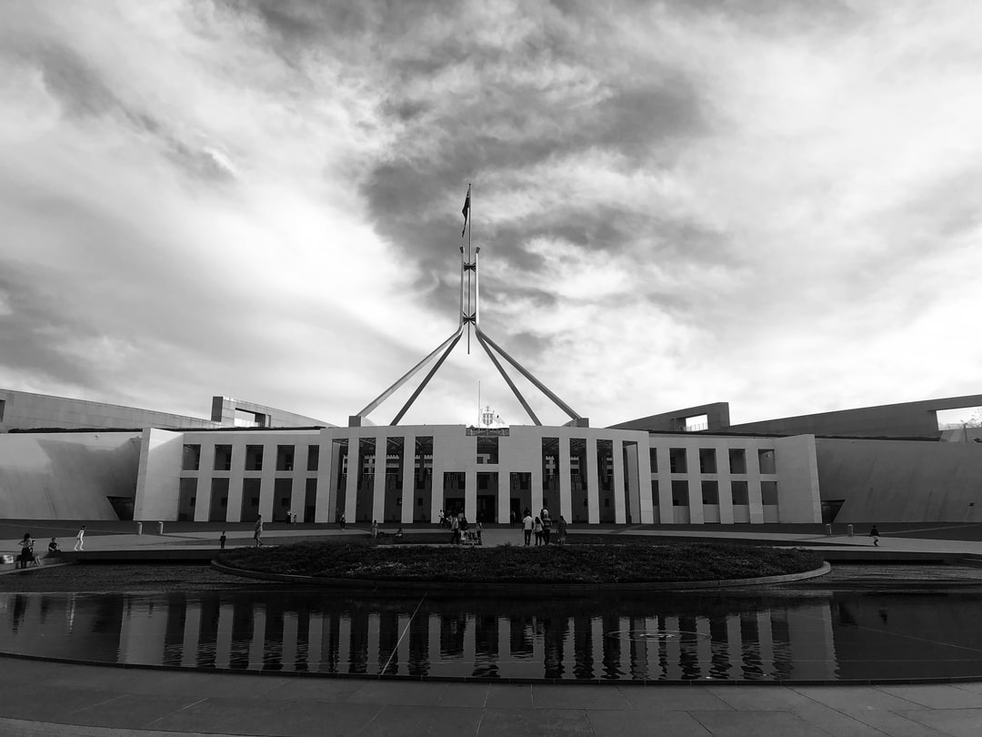 A large building with Parliament House, Canberra in the background